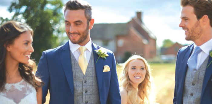 Wedding Suit Hire: The groom looking lovingly at his bride amongst his guests.