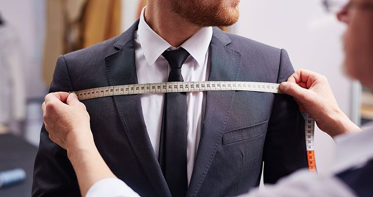 Testimonials - Derrick Dyas: A man in his suit getting his chest measured.